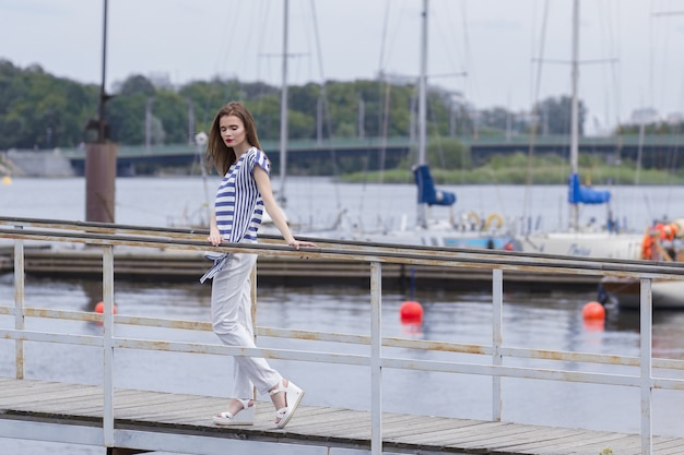 Bella donna in posa in una camicetta a righe e pantaloni bianchi al porto in una torbida giornata estiva,