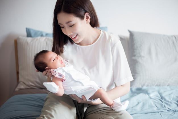 Bella donna in possesso di un neonato tra le braccia