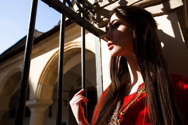 Bella donna in rosso sari sorge nelle ombre delle porte