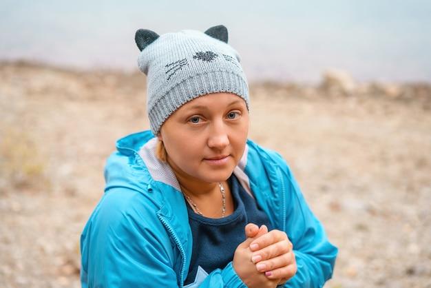 Bella donna in un cappello a maglia in una giacca blu