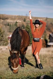 Bella donna in un cappello nero in posa con un cavallo