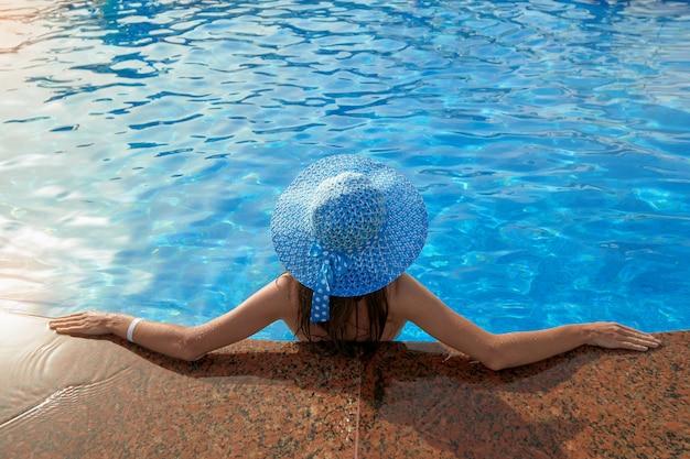 Bella donna in un cappello seduto sul bordo della piscina