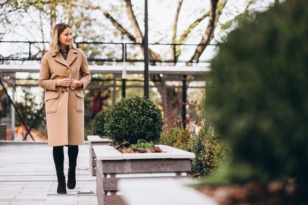 Bella donna in un cappotto beige fuori nel parco