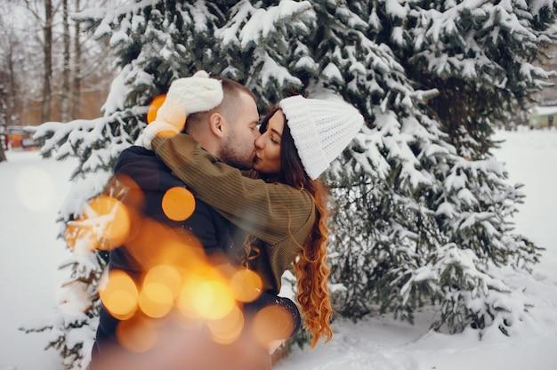 Bella donna in un parco invernale con suo marito