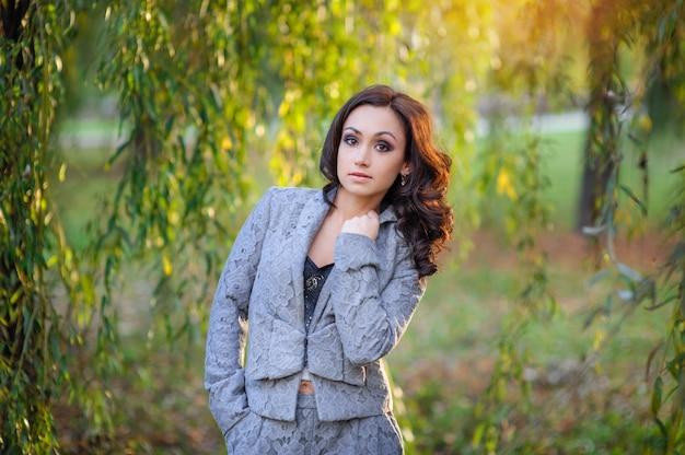Bella donna in un vestito grigio che cammina in primavera parco
