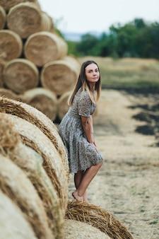 Bella donna in un vestito sui covoni di fieno.