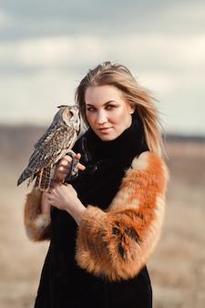 Bella donna in una pelliccia con un gufo a portata di mano