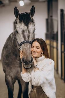 Bella donna in una scuderia con cavallo