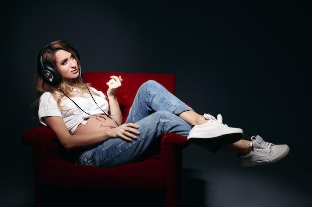 Bella donna incinta che si siede sulla sedia rossa e sulla musica d'ascolto.