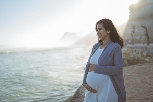 Bella donna incinta che sta sulla spiaggia
