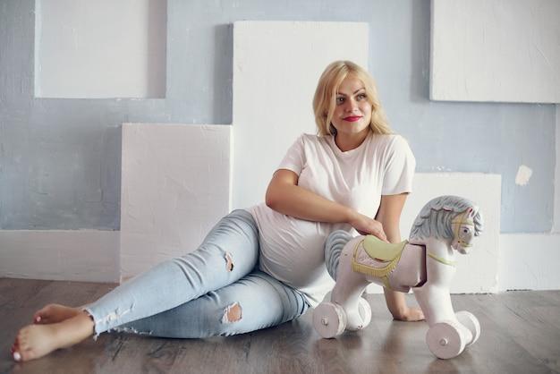 Bella donna incinta con la grande pancia in uno studio