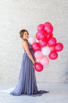 Bella donna incinta delicata con palloncini