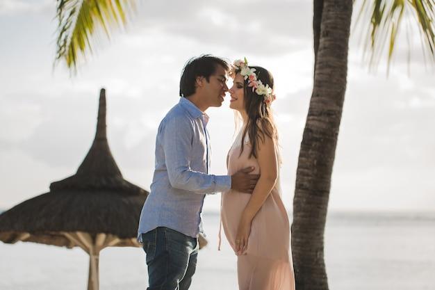 Bella donna incinta e uomo sulla spiaggia