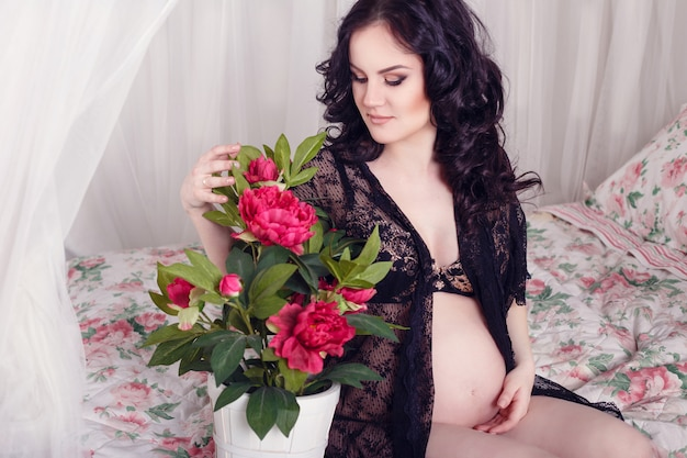 Bella donna incinta esile che si siede sul letto nella camera da letto. bella lingerie. gravidanza elegante e sexy.