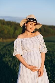 Bella donna incinta nel prato della natura di estate nel tramonto