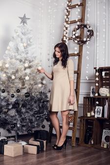 Bella donna incinta nella casa di inverno con l'albero di natale. , donna sorridente che celebra natale o capodanno. decorazione dell'albero di natale famiglia