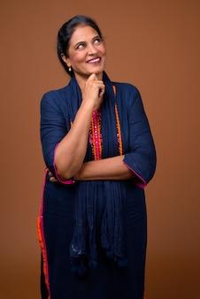 Bella donna indiana matura contro la parete marrone