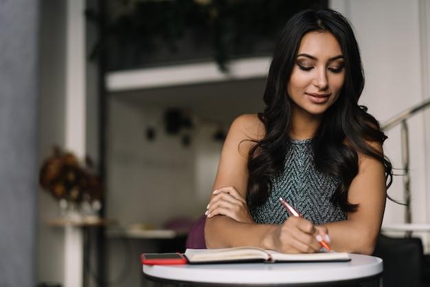 Bella donna indiana prendendo appunti, lavorando da casa. ritratto di riuscito scrittore asiatico seduto sul posto di lavoro