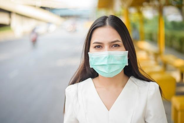 Bella donna indossa la maschera nella fermata dell'autobus