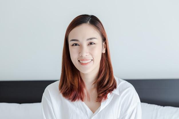 Bella donna indossare camicia bianca sorriso nella camera da letto al mattino