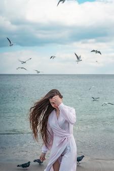 Bella donna insolita che cammina sulla spiaggia