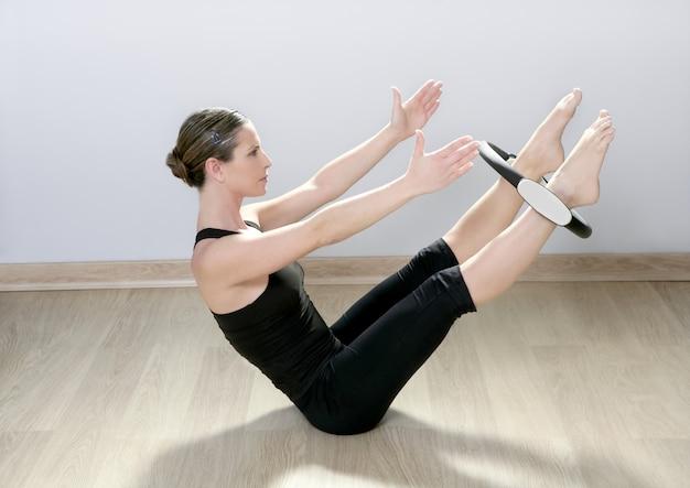 Bella donna istruttore con anello magico pilates in palestra sportiva