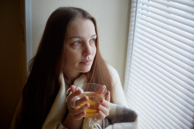 Bella donna malata con raffreddori e bevande tè caldo con limone seduto vicino alla finestra in una casa di campagna in inverno