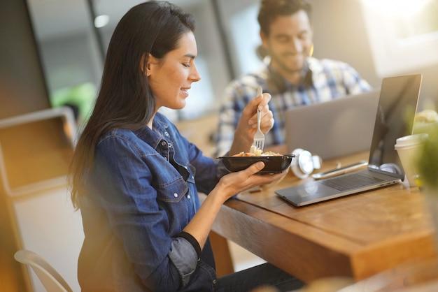 Bella donna mangiare pranzo mentre si lavora in co spazio di lavoro