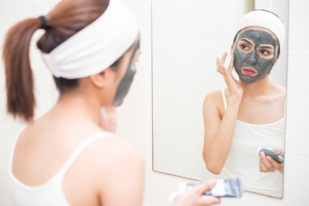 Bella donna mascherando il suo viso su sfondo bianco
