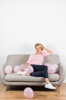 Bella donna matura che si siede sul divano con palloncini rosa