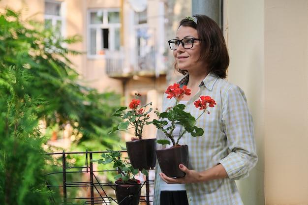 Bella donna matura con i fiori rossi in vaso di estate
