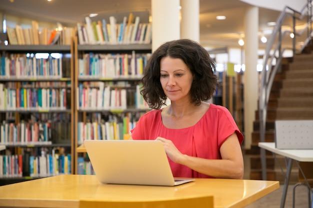 Bella donna messa a fuoco che esamina computer portatile mentre sedendosi alla tavola