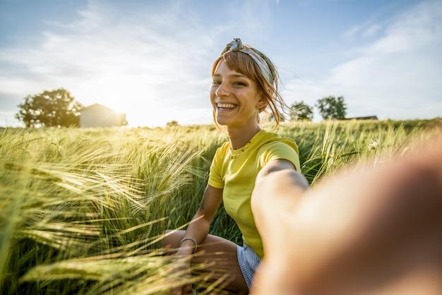 Bella donna millenaria felice che prende un ritratto del selfie con lo smartphone su un campo di grano all'estate. ritratto di una ragazza sorridente alla ricerca
