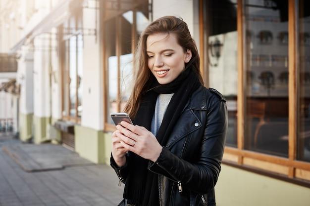 Bella donna moderna in abiti alla moda tenendo smartphone e guardando lo schermo mentre messaggistica o navigando in rete, camminando sulla strada