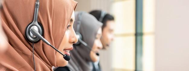 Bella donna musulmana asiatica che lavora nella call center con la squadra, insegna panoramica