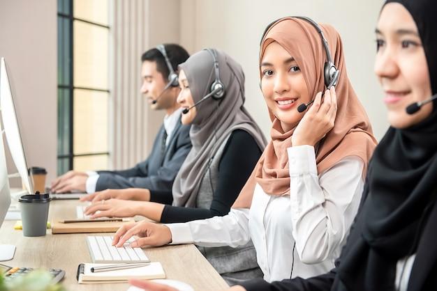 Bella donna musulmana asiatica che lavora nella call center con la squadra