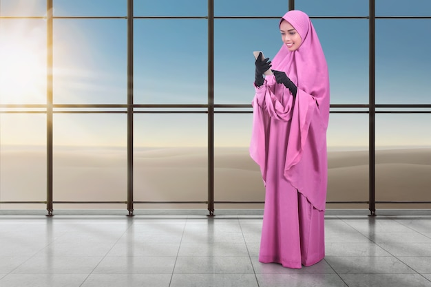 Bella donna musulmana asiatica che manda un sms sul cellulare