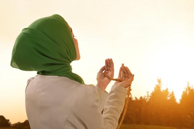 Bella donna musulmana asiatica che prega con i branelli di preghiera