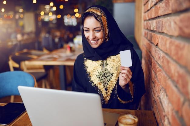 Bella donna musulmana sorridente seduto in un caffè, in possesso di carta di credito e guardando portatile. sulla scrivania di legno ci sono caffè e laptop.