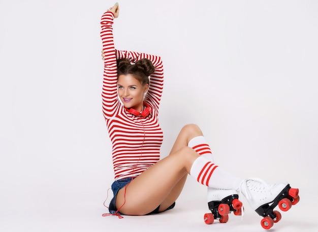 Bella donna nei pattini di rullo e con le cuffie rosse