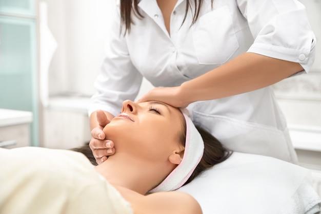 Bella donna nel salone spa, ricevendo il trattamento viso
