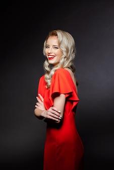 Bella donna nel sorridere rosso del vestito da sera