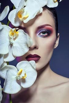 Bella donna nuda con un ramo di orchidea bianca