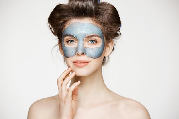 Bella donna nuda tenera in bigodini e maschera facciale sorridente. bellezza salute cosmetologia e cura della pelle.