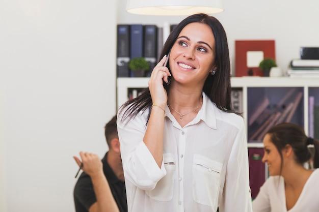 Bella donna parla al telefono in ufficio