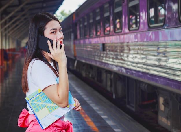 Bella donna parla al telefono mentre si aspetta il treno alla stazione ferroviaria.