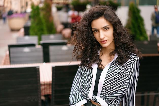 Bella donna per strada al caffè. capelli ricci scuri occhi castani. in posa per la fotocamera. ci sono tavoli e sedie nella parte posteriore