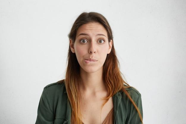 Bella donna perplessa con occhi scuri e capelli lisci tinti che si morde il labbro inferiore guardando con sorpresa. espressioni ed emozioni del viso umano.