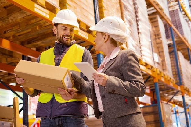 Bella donna piacevole che parla con il fattorino mentre controlla il servizio di consegna nel magazzino