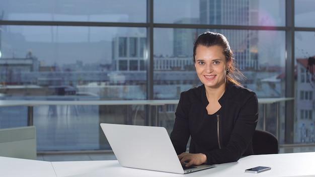Bella donna positiva che lavora facendo uso del computer portatile all'ufficio moderno